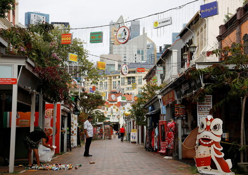 A man recycles aluminium drink cans in the largely empty Chinatown tourist district, Singapore