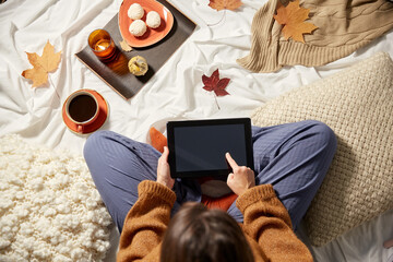 people, technology and leisure concept - young woman with tablet pc computer at home in autumn