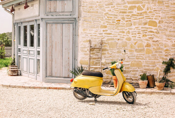 Nostalgic yellow scooter and plants by vintage building
