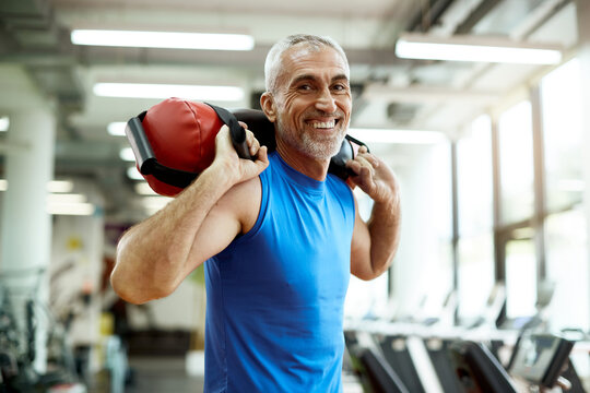 Happy mature sportsman exercises with sandbag during sports training at gym.