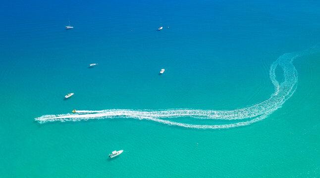Speedboats leave spray trail on sea water. Watersports at seaside aerial minimal background