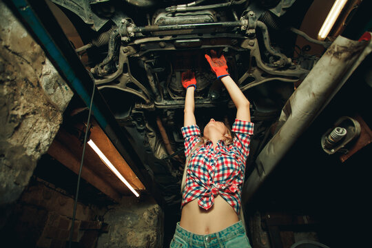 Handsome mechanic in uniform are working in auto service with lifted vehicle. Car repair and maintenance. Mechanic examining under the car at the repair garage.