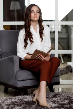 A young beautiful girl with a beautiful hairstyle and makeup in a white blouse and red trousers sitting in a chair with a book in her hands. Portrait of a model in office style clothes.