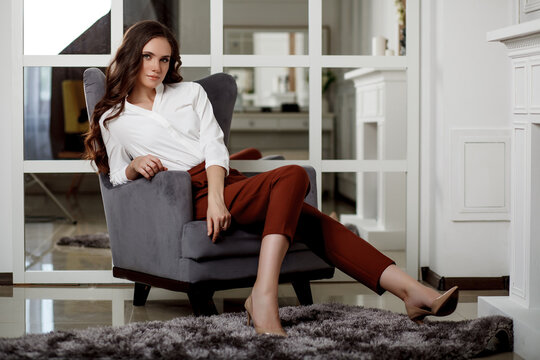 A young beautiful girl with a beautiful hairstyle and makeup in a white blouse and red trousers sitting in a chair. Portrait of a model in office style clothes.