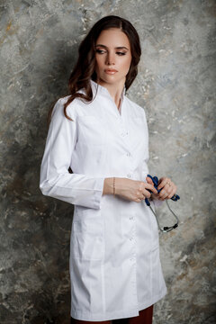 Tell me about your illnesses. Portrait of a beautiful girl with long wavy hair who stands in a white medical coat with a stethoscope.