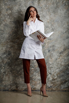 Portrait of a beautiful girl with long wavy hair. A female doctor in a white medical coat reading a large book thoughtfully.