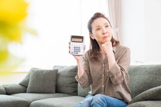 電卓を持つシニア女性 考える