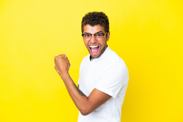 Young handsome Brazilian man isolated on yellow background celebrating a victory
