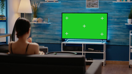 Young adult watching green screen display on television used for chroma key and modern copy space. Young adult using remote on mockup template and isolated background