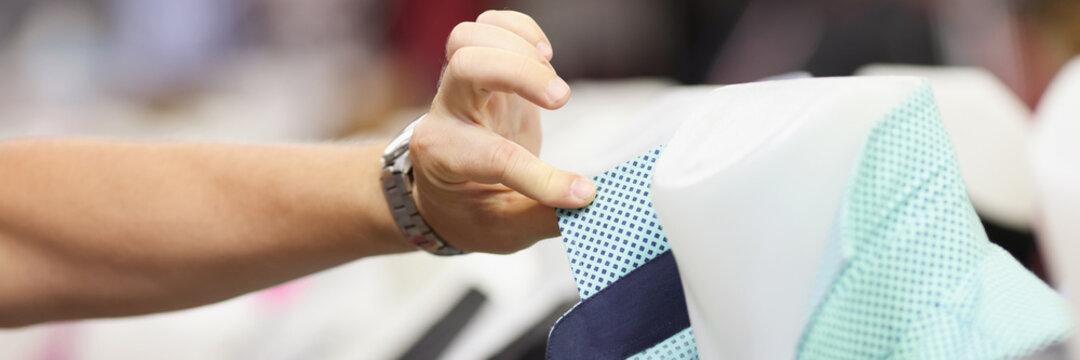 Seller hand adjusting collar of shirt on mannequin closeup