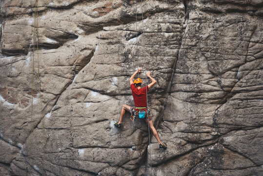 climber with safety rope is climb by vertical sandstone rock by well-trodden route orientate by rubbed stains