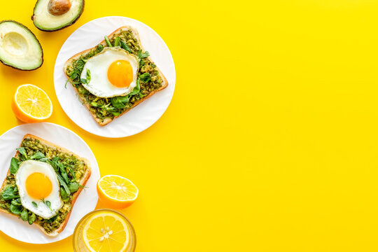 Breakfast with toasts of fried eggs and avocado saurce. Top view