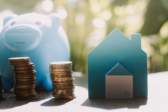 stacking money coins and a house model.save and investment for buy house concept .for the future.save money concept.