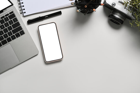 Mock up mart phone with empty screen, laptop, notebook and camera on white table.