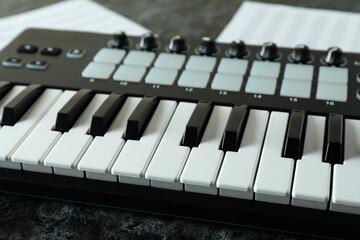 Midi keyboard and music sheets on black smokey table