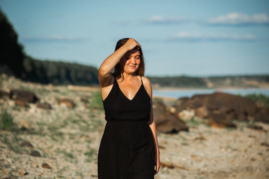 Beautiful young curvy woman in the black dress posing on the stones at sunset. Wild nature, natural beauty