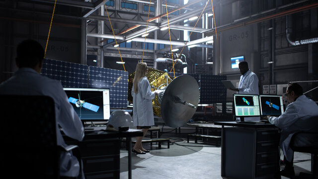 Engineer and Technician Working on Satellite Construction. Aerospace Agency: Diverse Team of Scientists Using Technological Equipment and Laptop Computer to Develop Spacecraft for Space Exploration.