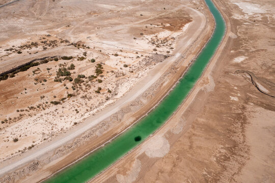 Salt water canal leading Dead Sea water to evaporation pools, Aerial view.
