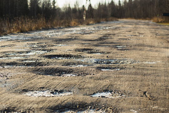 Autumn dirty gravel road with hoarfrost covered potholes. It has some surface damage, needs maintenance, hole patching, dust binding and dragging