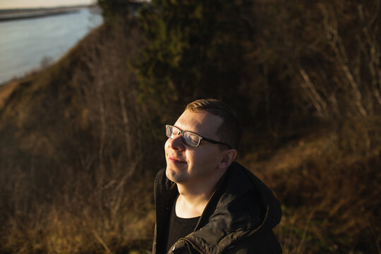 A young man in glasses enjoys the beautiful autumn nature on a sunny autumn day in the forest