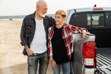 Smiling father and his son sitting in a car trunk