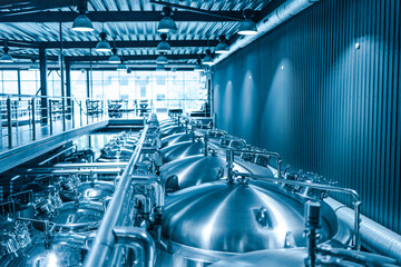 Obraz Private microbrewery. Modern beer plant with brewering kettles, tubes and tanks made of stainless steel - fototapety do salonu