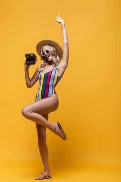 full length of amazed woman in straw hat and swimsuit holding vintage camera on yellow.