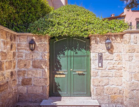 stylish house, green metallic door and stone wall fence with lots of foliage, Athens Greece