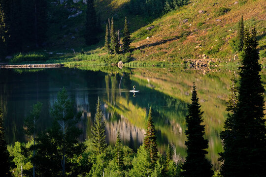 Person Paddle Boarding on High Mountain Lake