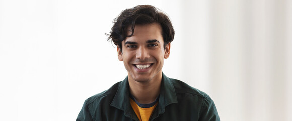 Portrait of happy caucasian young man looking at the camera and smiling