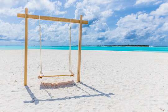 wooden swing on a white sand beach on the Indian Ocean in the Maldives
