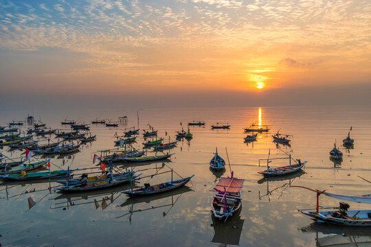 Sunrise on Bulak beach, Kenjeran, Surabaya with a fishing boat in the background