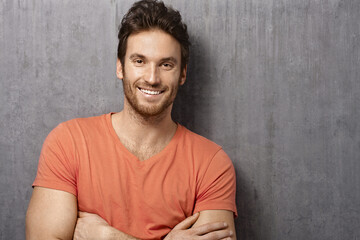 Portrait of happy white young man smiling, standing against white concrete wall. Copy space, casual clothing.