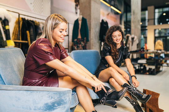Beautiful young women trying leather boots in expensive boutique or store.