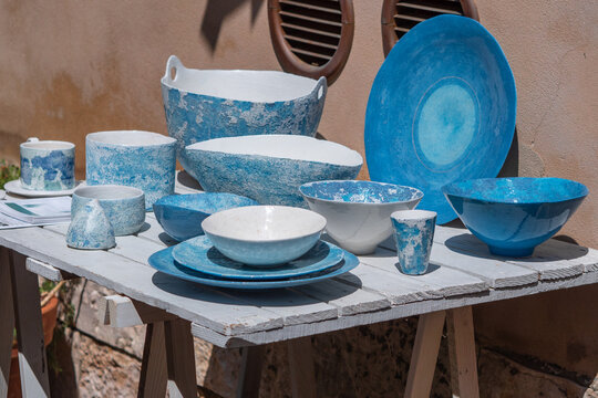 Blue and White Ceramic Plates, Vases, and Cups displayed on a Wooden Table Outdoors