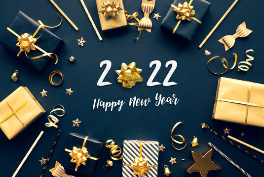 2022 happy new year celebration concepts with gift box and ornament in golden color on dark background.