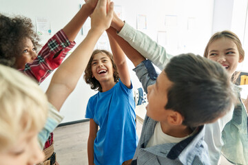 Fototapeta Happy diverse multiethnic kids junior school students group giving high five together in classroom. Excited children celebrating achievements, teamwork, diversity and friendship with highfive concept. obraz