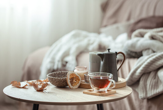 A cup of tea and a teapot on a blurred background of the interior of the room.