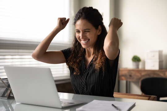 Happy excited millennial businesswoman in casual excited with good news at laptop, looking at screen, celebrating win, achieve, approved loan, making yes hand gesture. Employee getting job promotion.
