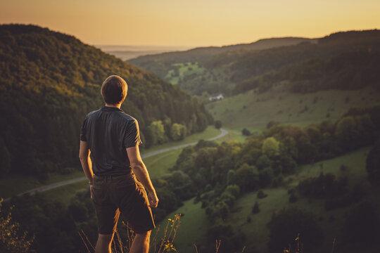 Sportlicher junger Wanderer im Sonnenuntergang in Oberfranken in den hügeligen Wäldern
