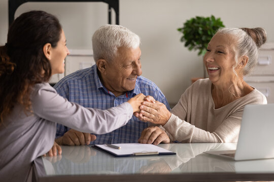 Happy senior couple of clients meeting with real estate or insurance agent, shaking hands with realtor, broker, thanking lawyer for consultation, help with document filling, giving handshake
