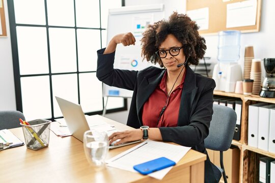 African american woman with afro hair working at the office wearing operator headset strong person showing arm muscle, confident and proud of power