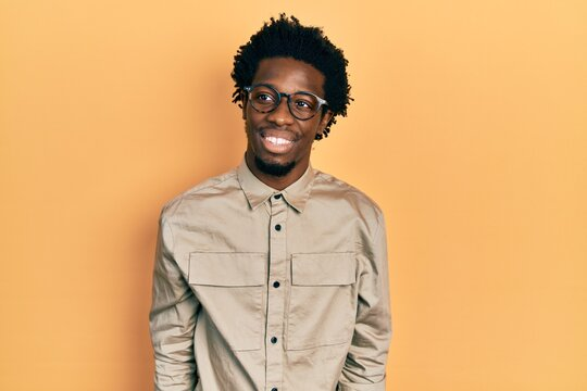Young african american man wearing casual clothes and glasses looking away to side with smile on face, natural expression. laughing confident.