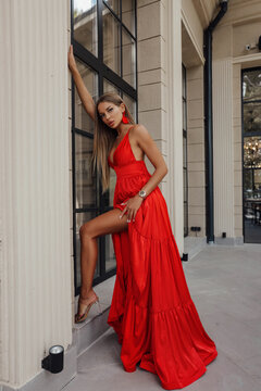 beautiful woman with blond hair in luxurious evening dress posing outdoor