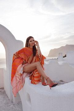 beautiful woman with dark hair in elegant dress posing outdoor