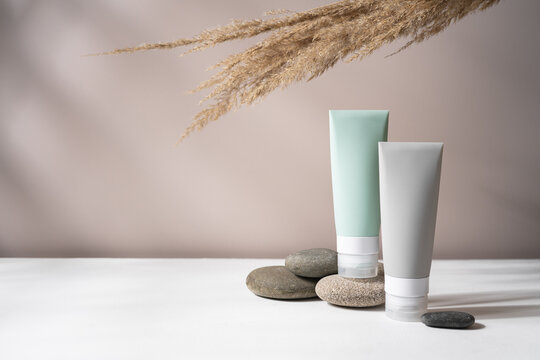 Cosmetic bottles on pebble stone podium with dry plants on the background. Background for cosmetic product branding, identity and packaging