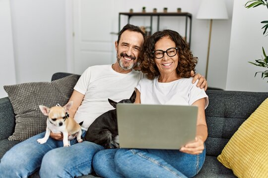 Middle age hispanic couple smiling happy and using laptop. Sitting on the sofa with dogs at home.