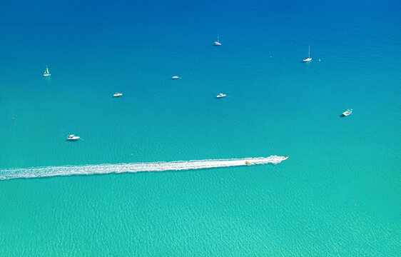 Speedboat and wave slider leaving trail on water, with other boats and sea as background with copy space. Aerial seascape