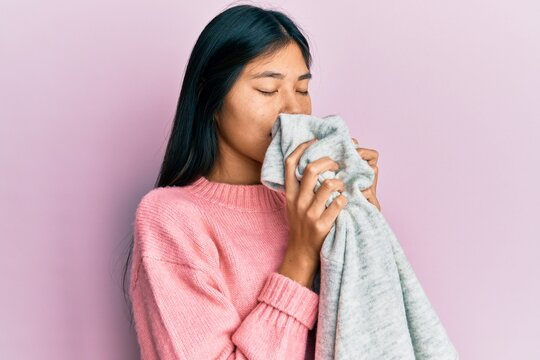 Young asian woman smelling laundry scent from clean sweater