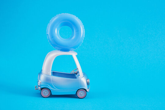 toy car and lifebuoy on the roof, swimming circle on the roof of a small blue golf car on a blue background